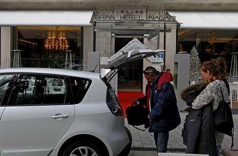 Unos clientes descargan las maletas del coche para entrar en un hotel de Vigo.