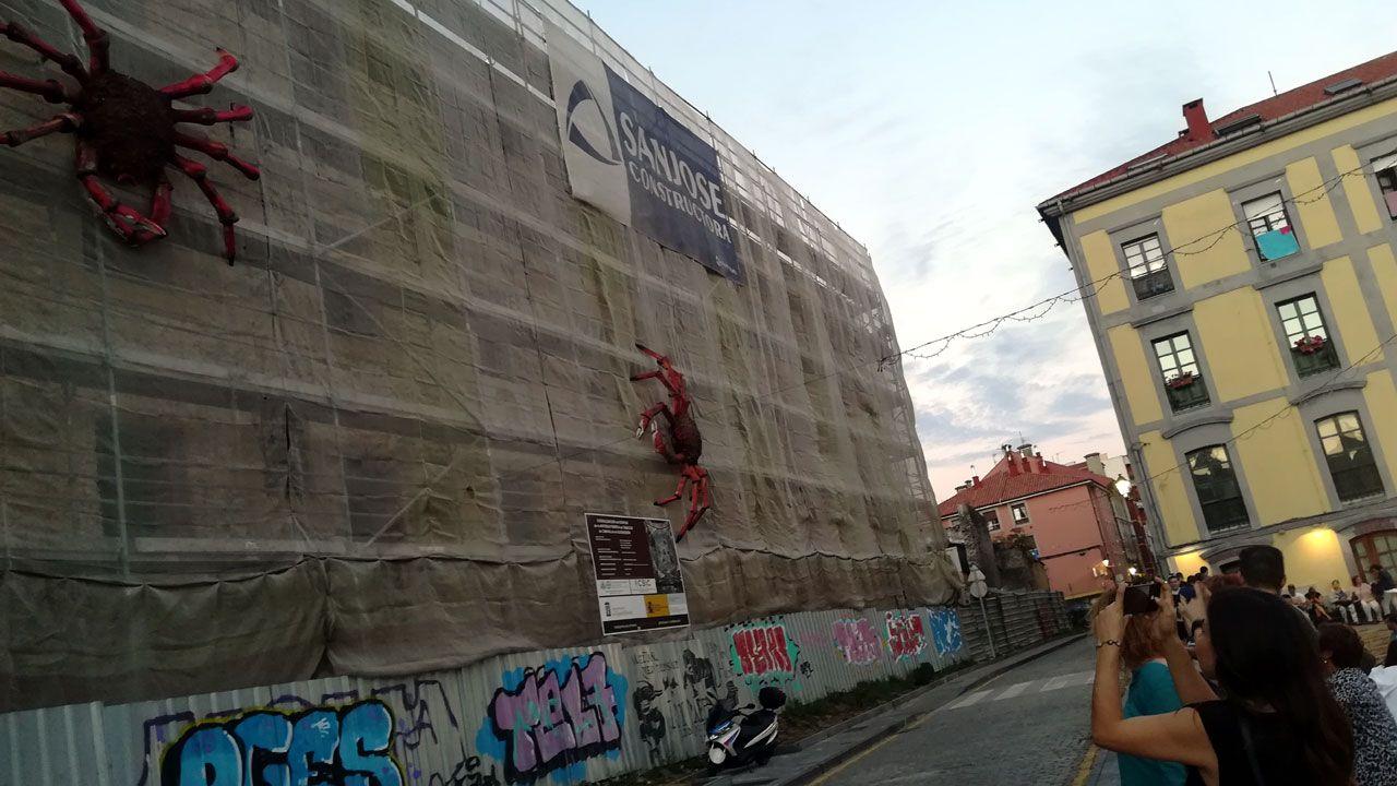 Una joven fotografía la decoración de la fachada de Tabacalera durante las fiestas de Cimavilla