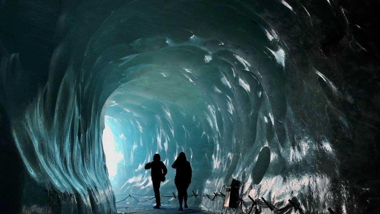 Visitantes caminan a través de una cueva de hielo artificial dentro del glaciar del valle Mer de Glace, uno de los más grandes de los Alpes