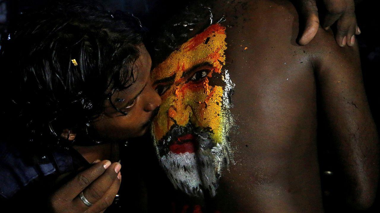 .Un fan besa la imagen del actor Rajinkanth pintada en el cuerpo de otro seguidor para celebrar el lanzamiento de su nueva película, en Bombay