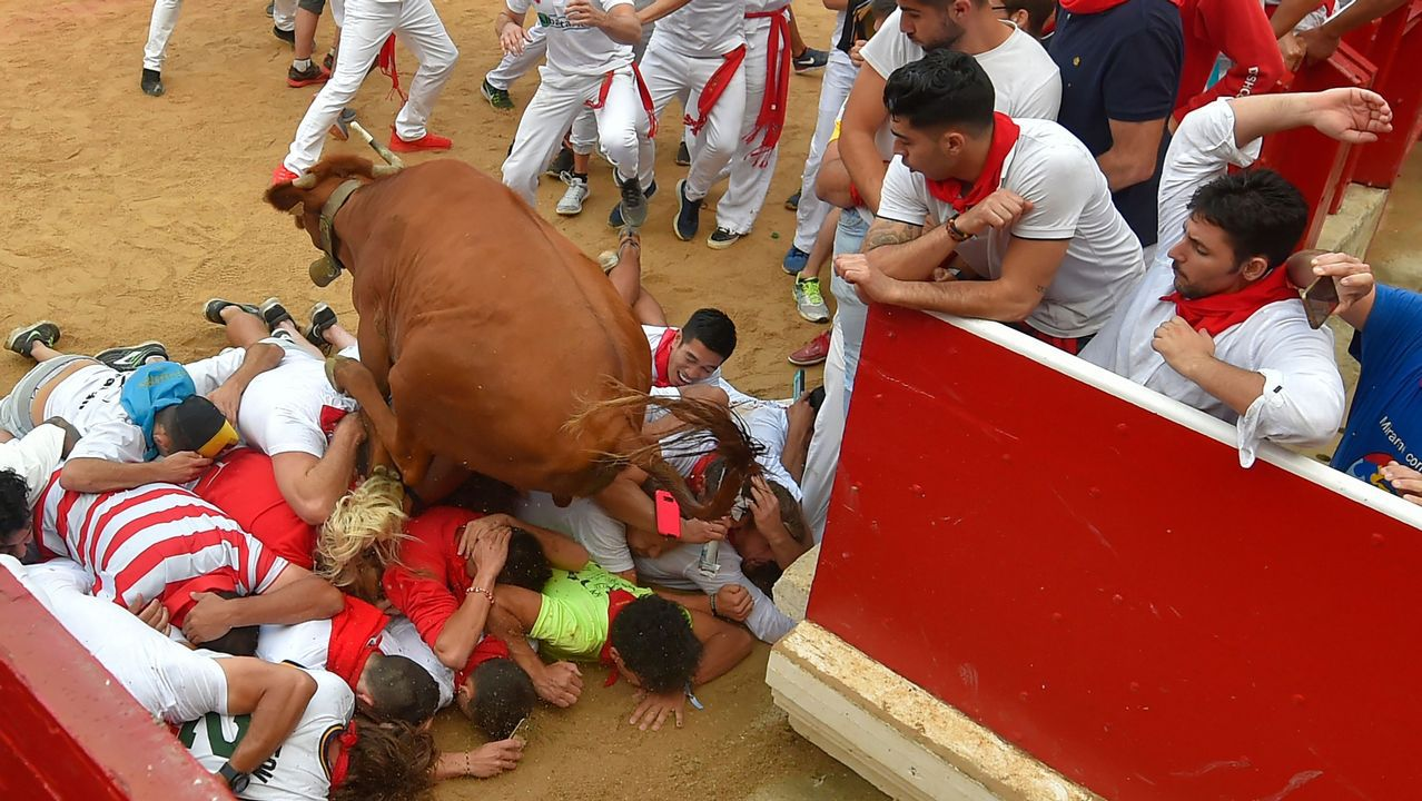 Un toro entra en la plaza de Pamplona pasando sobre varios participantes en el encierro, durante la jornada de hoy de sanfermines