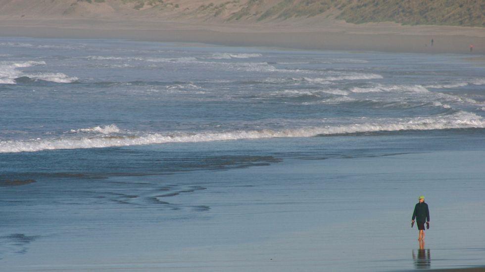 Un grupo de personas pasea por una playa del centro de Asturias.Un grupo de personas pasea por una playa del centro de Asturias