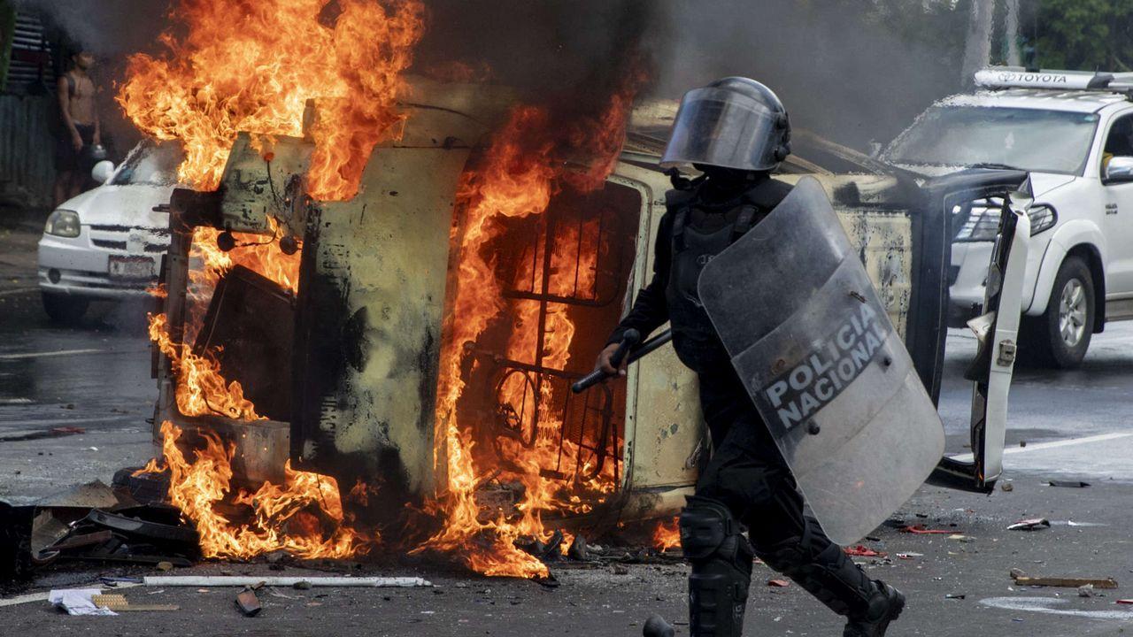 Un integrante de la Policía de Nicaragua pasa frente a un vehículo policial ardiendo en Managua
