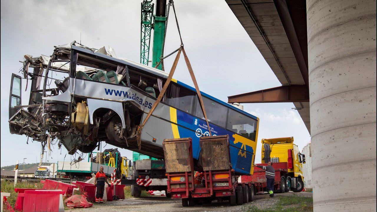 Una grúa retira los restos del autobús de la compañía Alsa que hoy se ha empotrado contra una pilastra de hormigón de un paso elevado de la circunvalación de Avilés, en un accidente de tráfico que ha causado al menos cinco fallecidos y una quincena de heridos de diversa consideración.