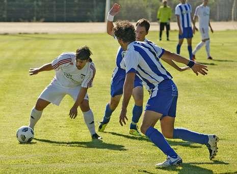 Dos futbolistas del Taboada intentan interceptar la internada de un contrario en A Medela.