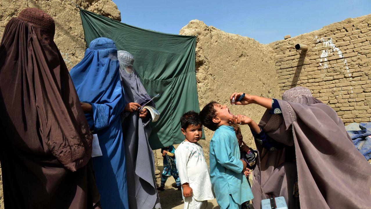 .Un trabajador de salud afgano administra la vacuna contra la polio a un niño, mientras otros miembros del equipo de campaña de vacunación usan burkas en el distrito de Arghandab de Kandahar