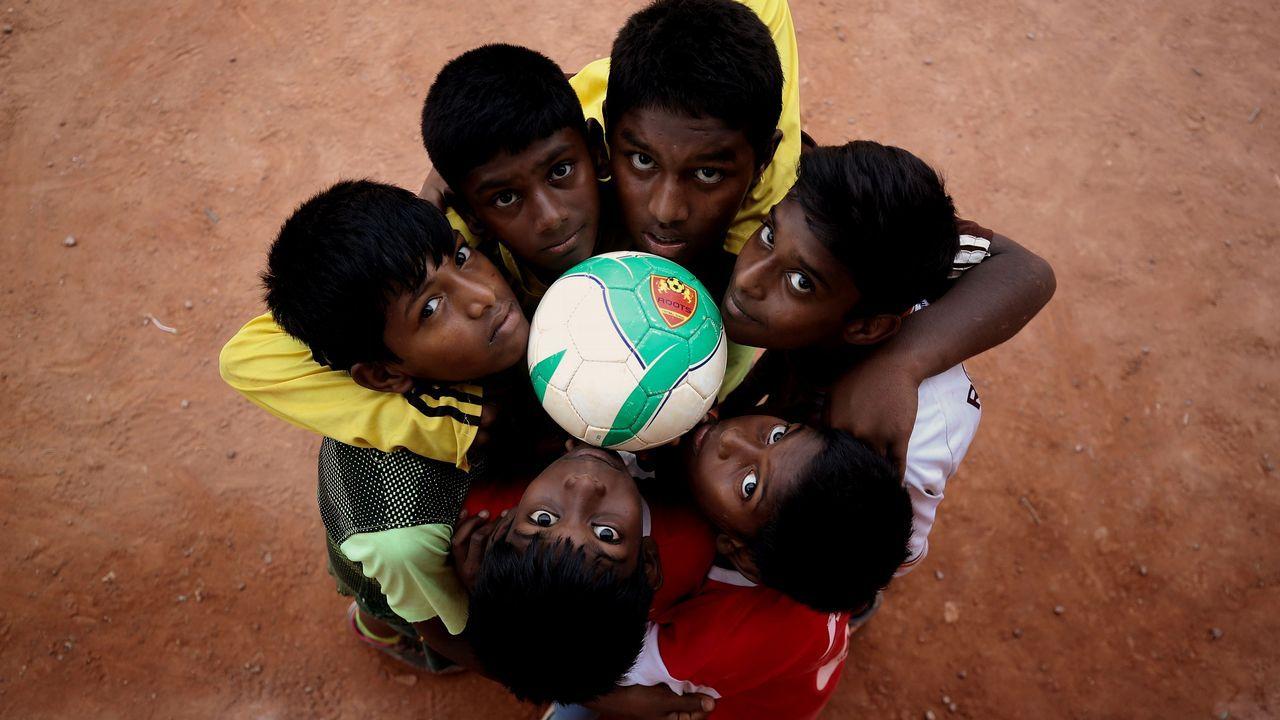 .Aficionados del fútbol indio posan con una pelota en Gauthampura, Bangalore, India