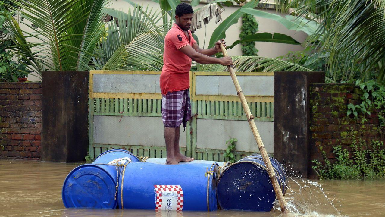 Un hombre usa una balsa hecha a mano para cruzar una calle inundada en Cochín, Kerala, India, hoy 10 de agosto de 2018. Al menos 20 personas han muerto en el sur de la India, la mayoría de ellas a causa de los deslizamientos de tierra que han provocado las fuertes lluvias en la región