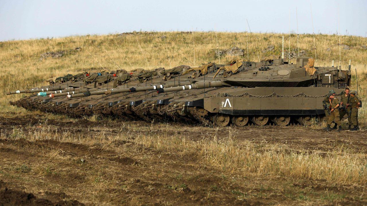 .Soldados israelíes se paran junto a los tanques Merkava Mark IV en un área de despliegue de los altos del Golán, área siria que ocupa militarmente
