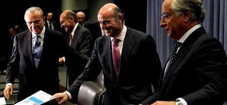 Isidro Fainé y Juan María Nin, presidente y consejero delegado de Caixabank, con el ministro Luis de Guindos el pasado octubre.