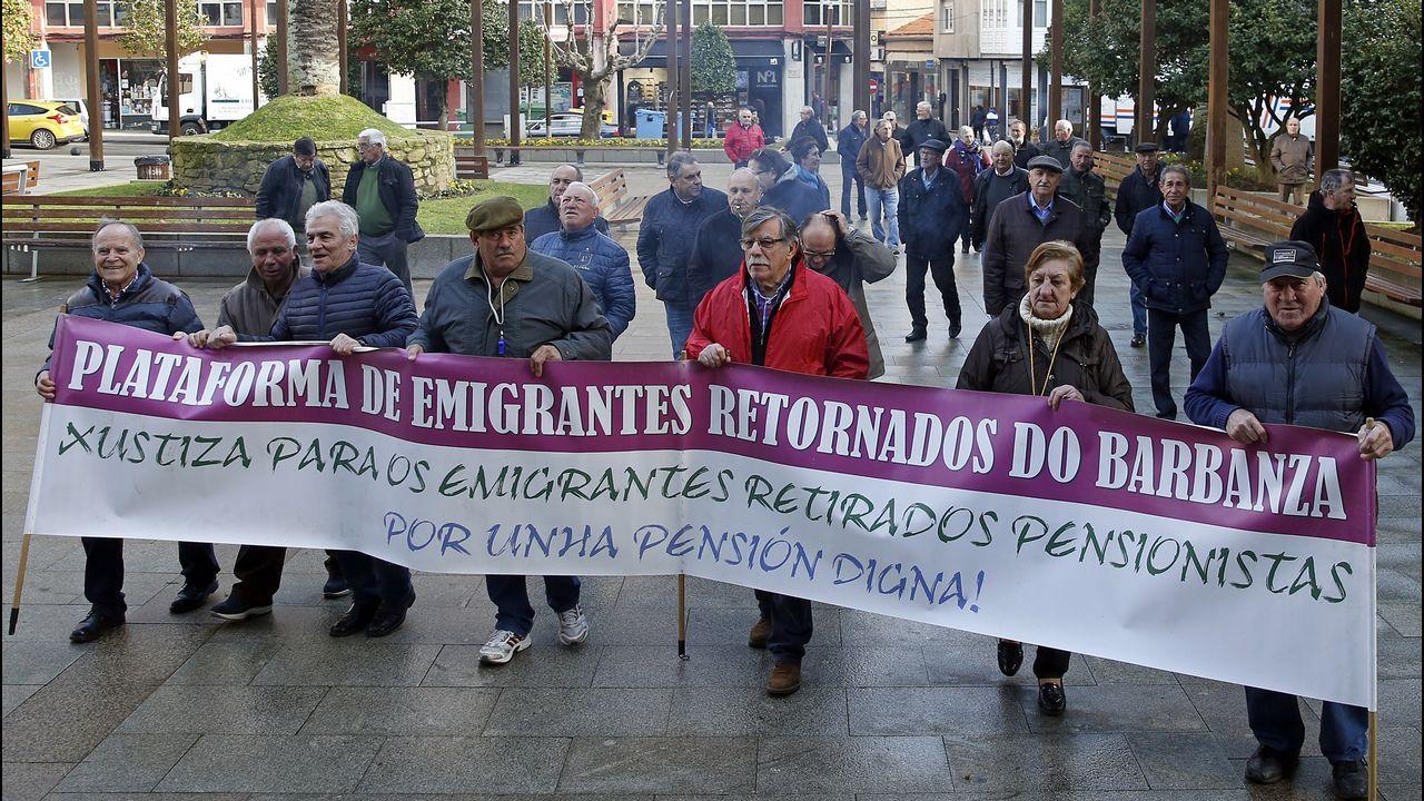 Un autobús simula la emigración asturiana de Tineo, durante el desfile del Día de América en Asturias.La escultura 'La madre del emigrante', en Gijón