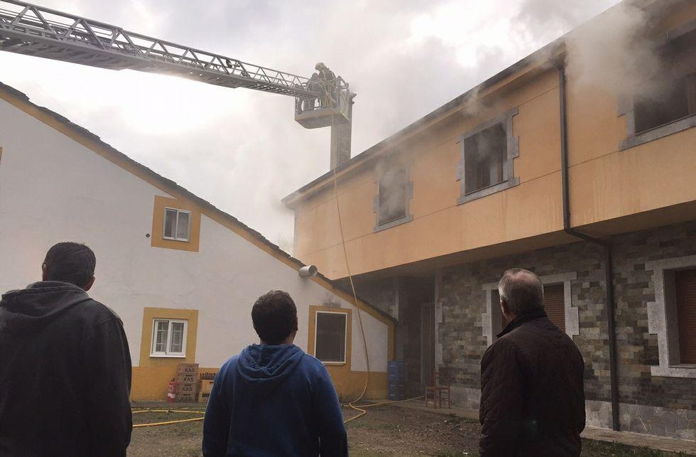 Los vecinos de la zona observando la situación y los bomberos apagando el incendio.