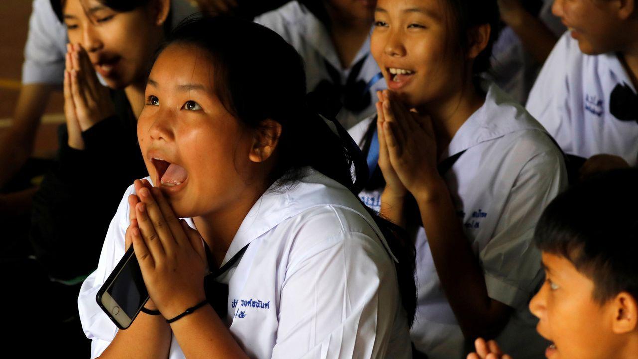 .La emoción de unos escolares tailandeses cuando el profesor les anuncia que ya están a salvo cuatro de los menores atrapados en la cueva