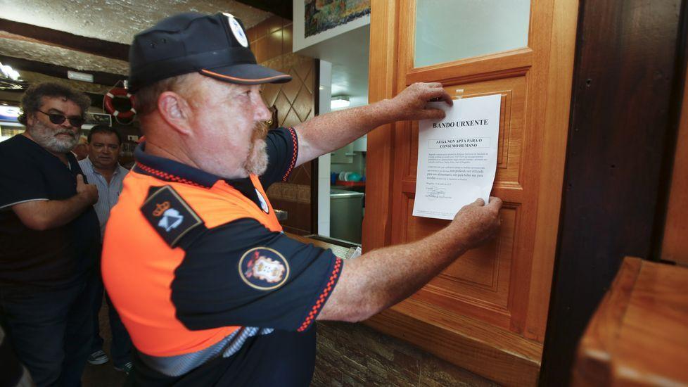 Miembros de protección civil de Mugardos colocan un bando municipal en establecimientos hostelereos alertando de la restricción