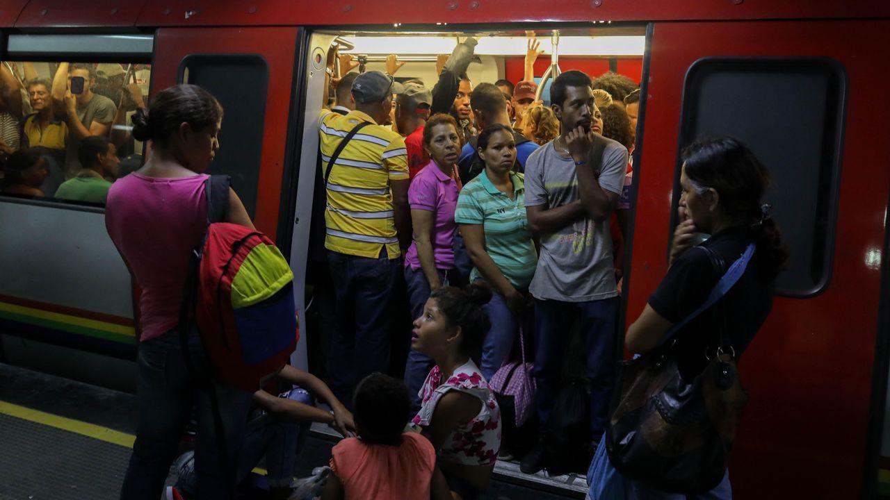 Personas aguardan la reanudación del Metro de Caracas después de una interrupción del servicio tras un corte de energía