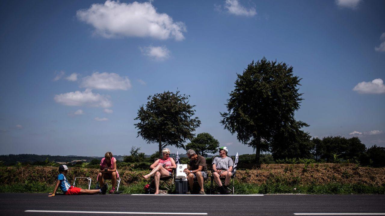 Un grupo de aficionados esperan en Mur-de-Bretagne el paso de los ciclistas durante la jornada de hoy del Tour de Francia