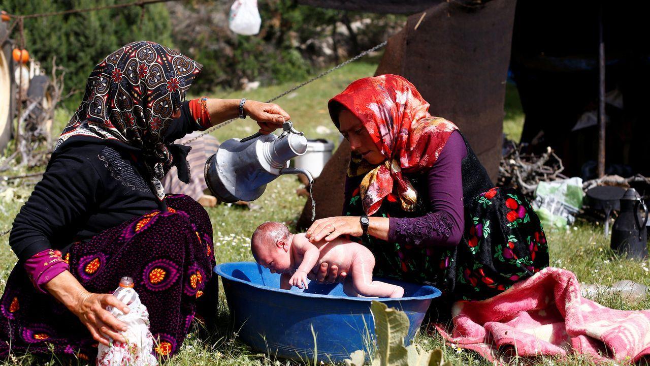 Dos mujeres nómadas bañan a un bebé durante su viaje anual a la provincia central de Anatolia, en Turquía