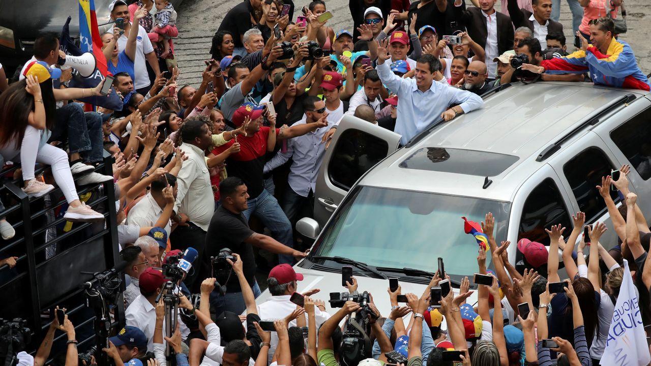 Un grupo de pasajeros consulta los vuelos en el Aeropuerto de Asturias.- Un grupo de personas protesta por la falta de agua potable y electricidad, en la Avenida Baralt, en el centro de Caracas