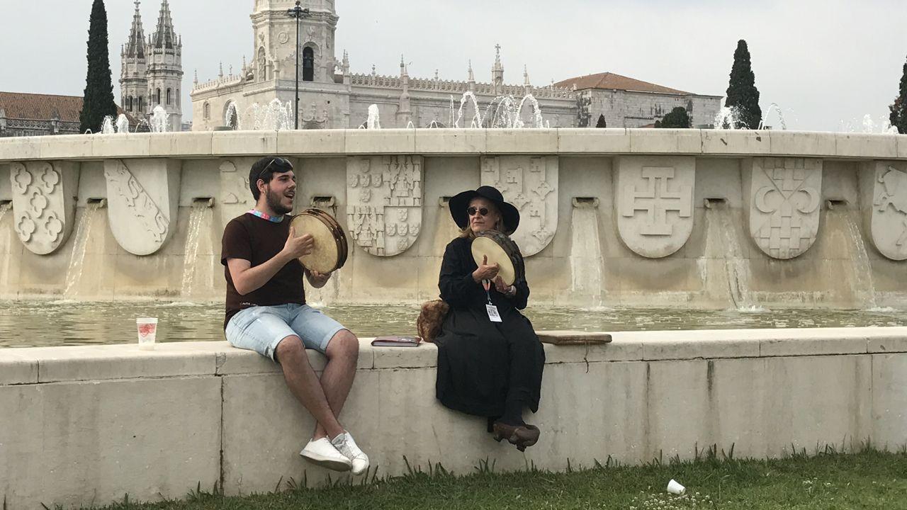 El personaje de la ciega y uno de los músicos de la Bandina Lèmbolau tocan la panderera con el Monasterio de los Jerónimos al fondo