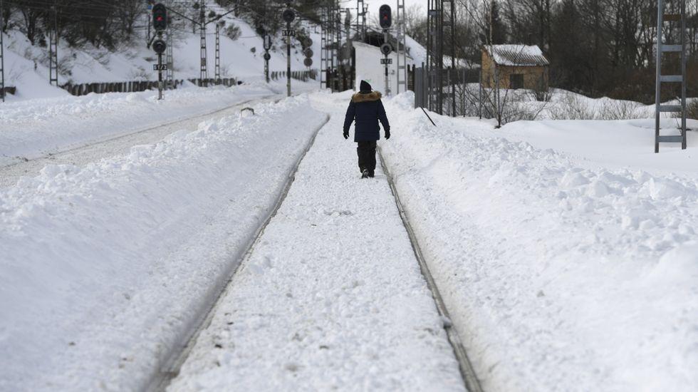 Un hombre muestra el espesor de la nevada en Riofrío, en la vertiente asturiana de San Isidro.Un hombre camina entre las vías del tren heladas en Busdongo