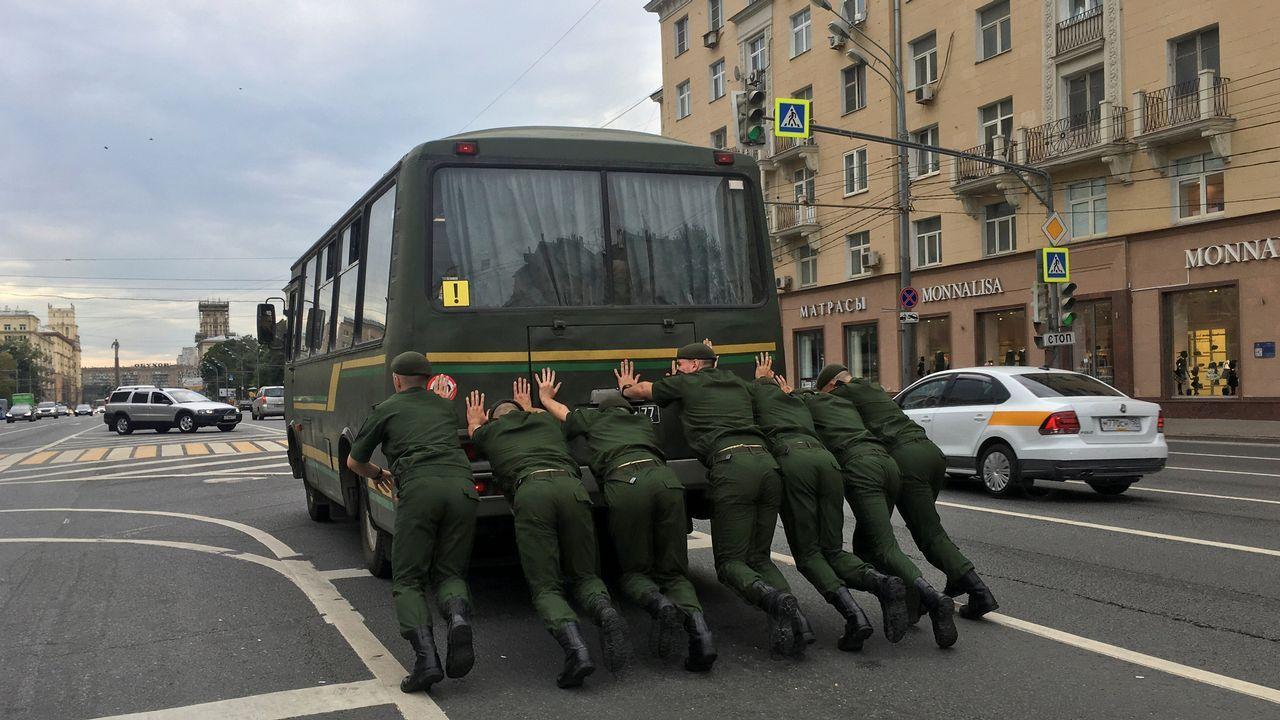 Varios miembros de las fuerzas de seguridad rusas empujan un autobús en Moscú.