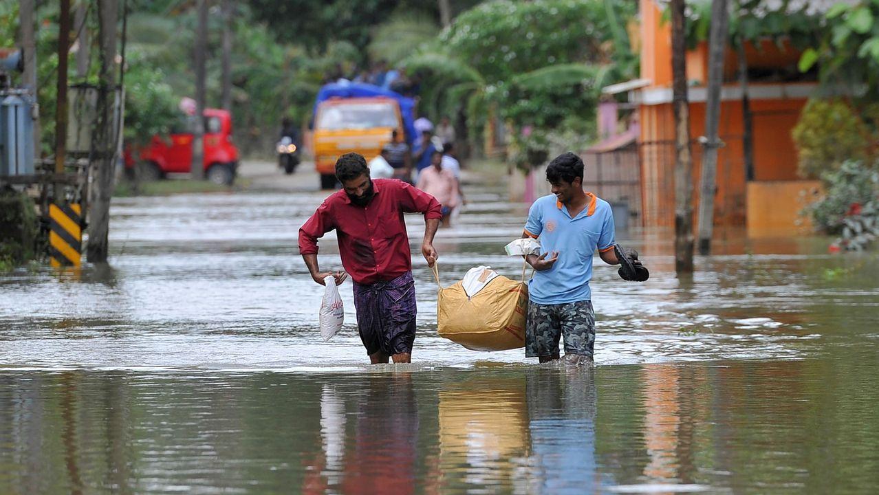 Hombres indios transportan alimentos y agua para las personas atrapadas por las inundaciones en Pandanad, al sur de la India