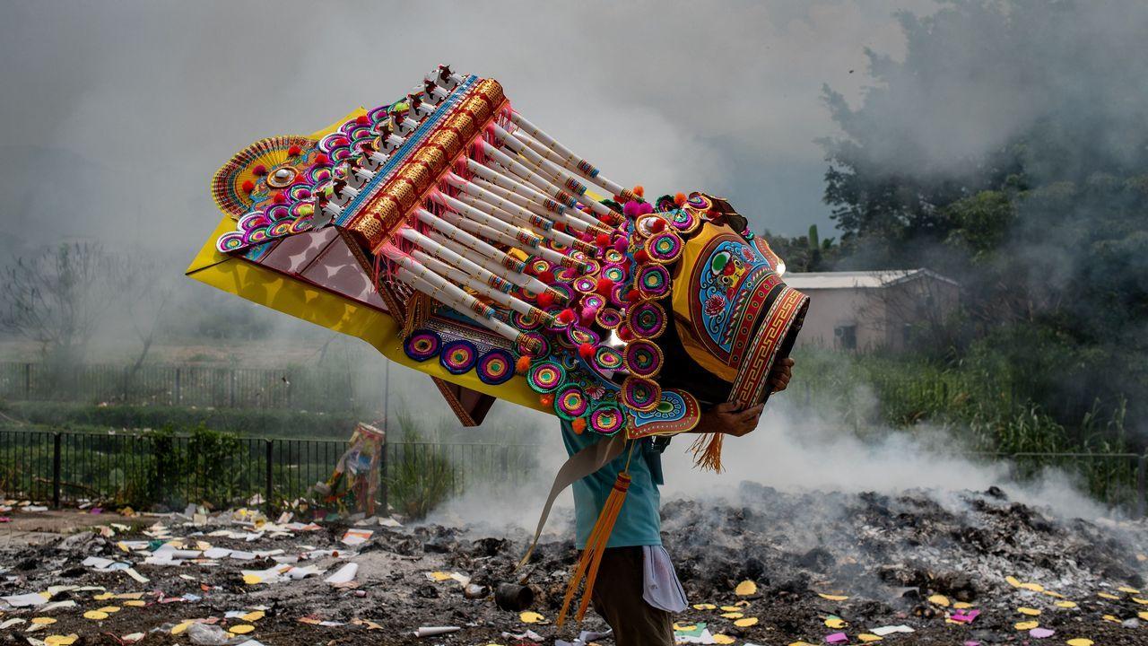 Los devotos mueven una parte de una gran estatua de papel tradicional china durante un evento para conmemorar el Hungry Ghost Festival en Hong Kong.