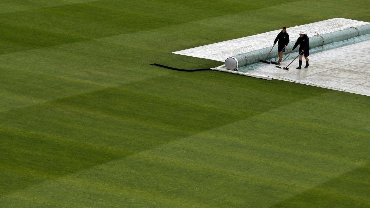 El personal de tierra barre el agua mientras la lluvia retrasa el inicio del juego el primer día del segundo partido de prueba de cricket entre Inglaterra y la India en Lord's Cricket Ground en Londres