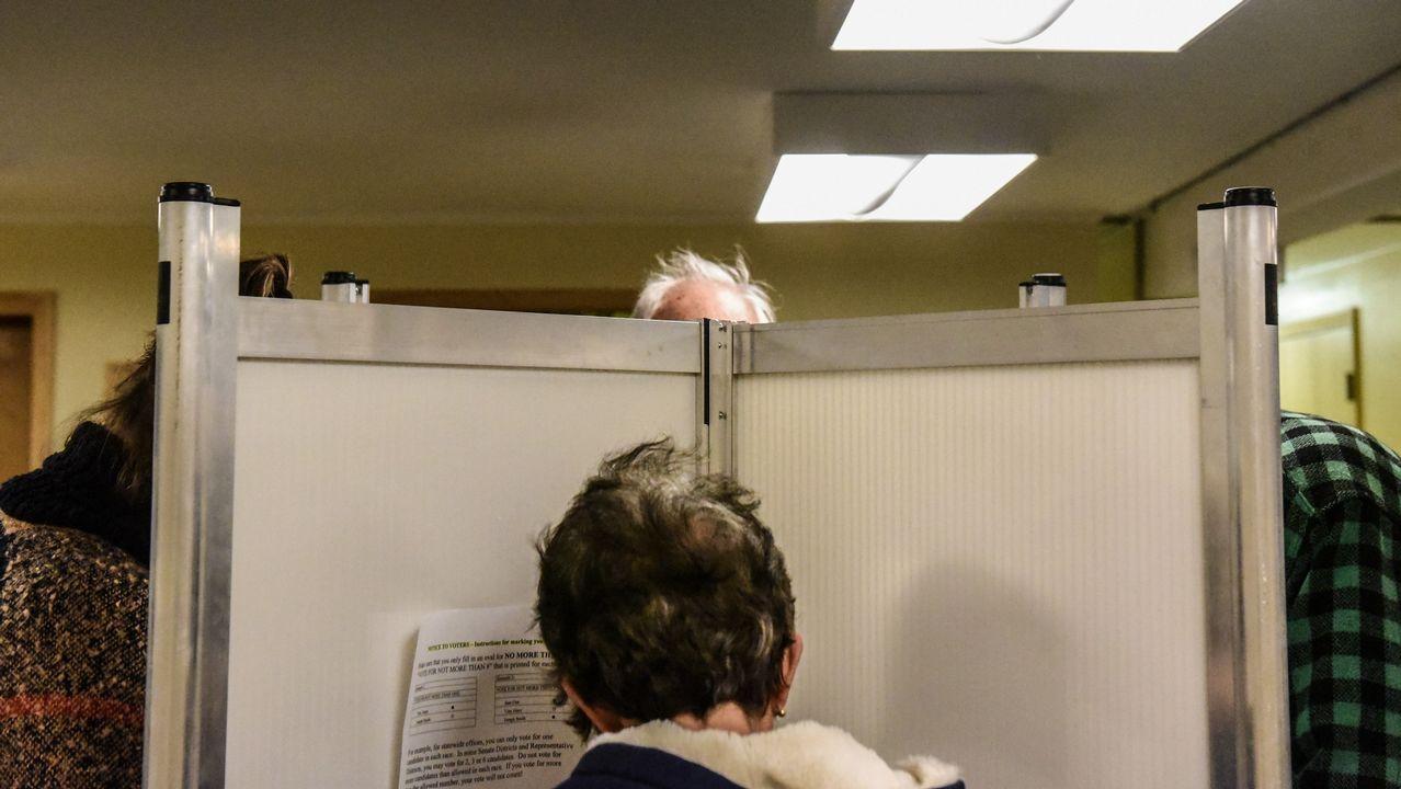 Dos personas votando en cabinas, en Vermont