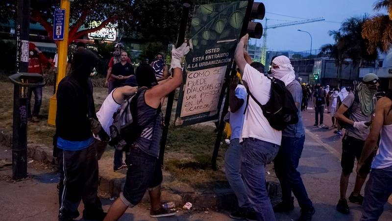 Duros enfrentamientos en Venezuela.Los agentes intentan apresar a un manifestante en pleno centro turístico de Río.