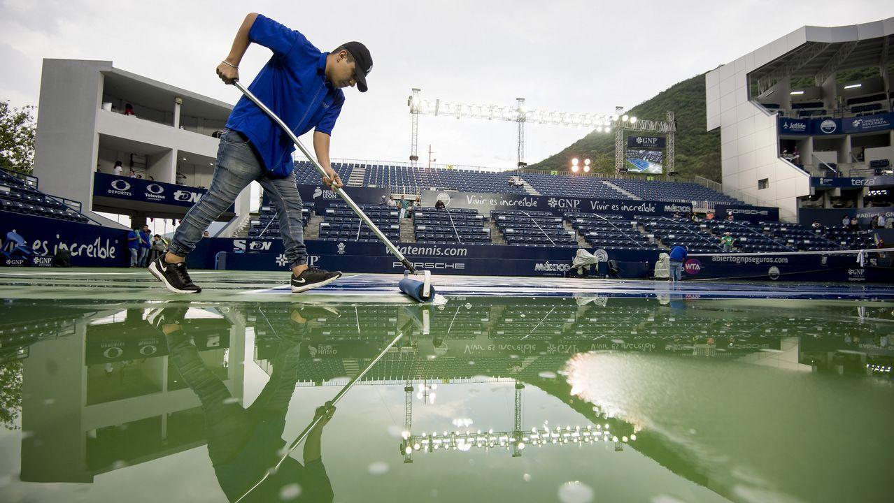 Miembros de logística secan la cancha del partido entre la checa Marie Bouzkova y la húngara Timea Babos, en el Abierto de Tenis de Monterrey, en México