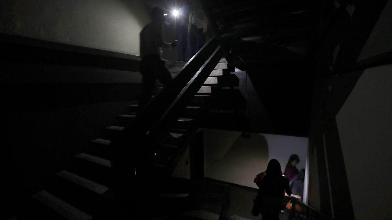 Un grupo de pasajeros consulta los vuelos en el Aeropuerto de Asturias.Dos personas transitan por la escalera de un edificio a oscuras de la capital venezolana
