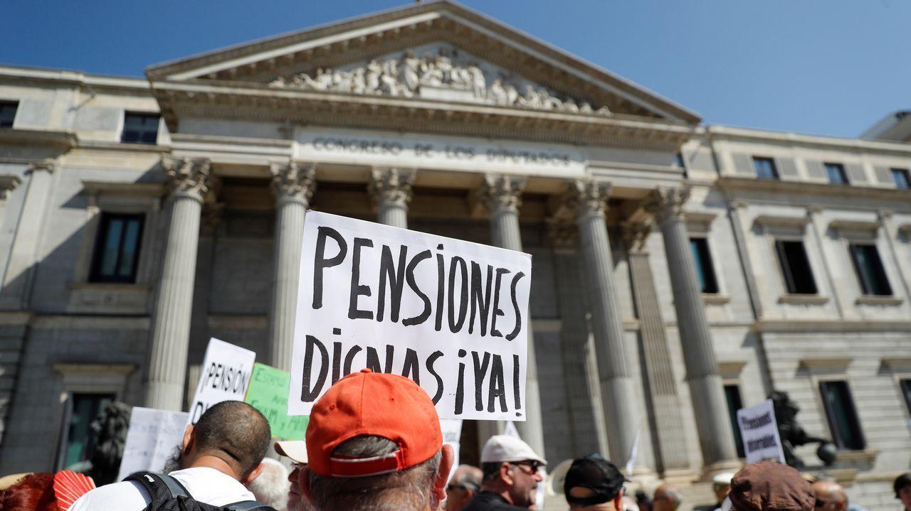 Tensa protesta de pensionistas a las puertas del Congreso.Cruz del Valle de los Caidos, bajo la que está enterrado Franco