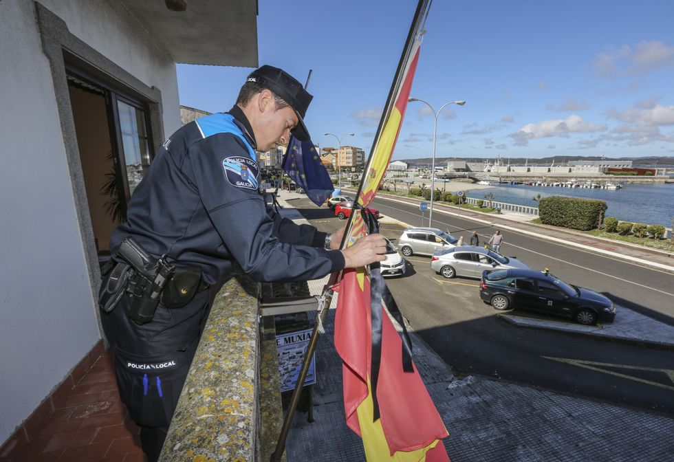 Las caras de la lista «renovada» de Feijoo.Un policía local coloca un crespón negro en la bandera española, que quedó izada a media asta.