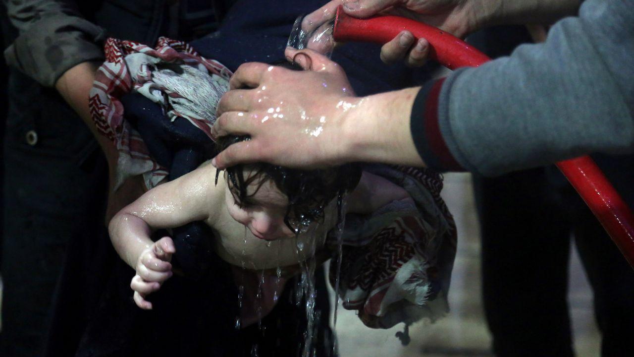 .Un grupo de sanitarios del hospital de Duma lavan con agua a un bebé afectado tras el ataque de sábado con gas cloro