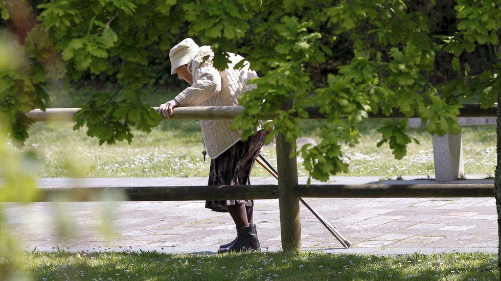 Oposiciones.Una anciana pasea por un paseo fluvial