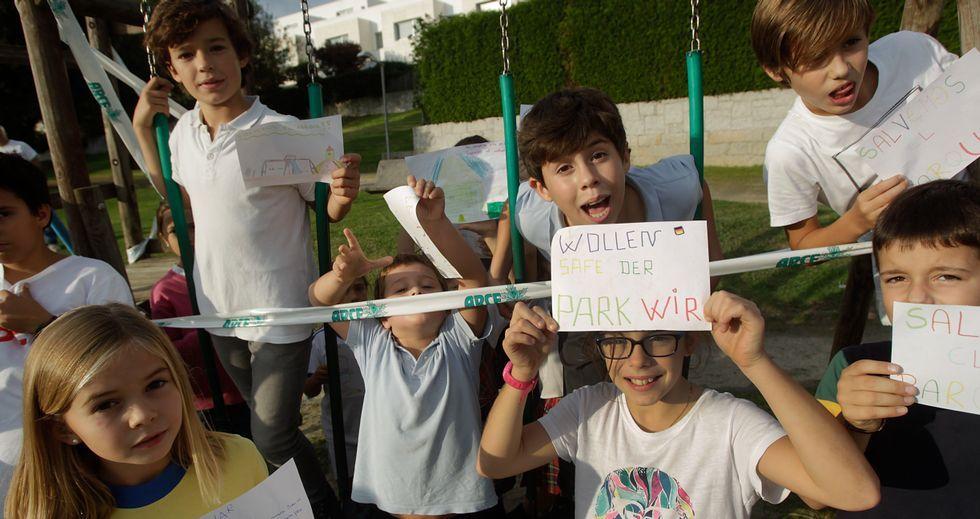Un grupo de niños de la urbanización muestra sus reivindicaciones junto al juego infantil precintado tras la rotura de un travesaño.