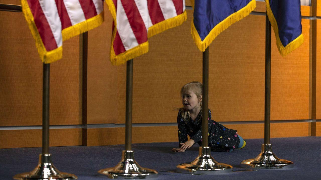 .Una niña juega detrás de una serie de banderas en la Casa Blanca