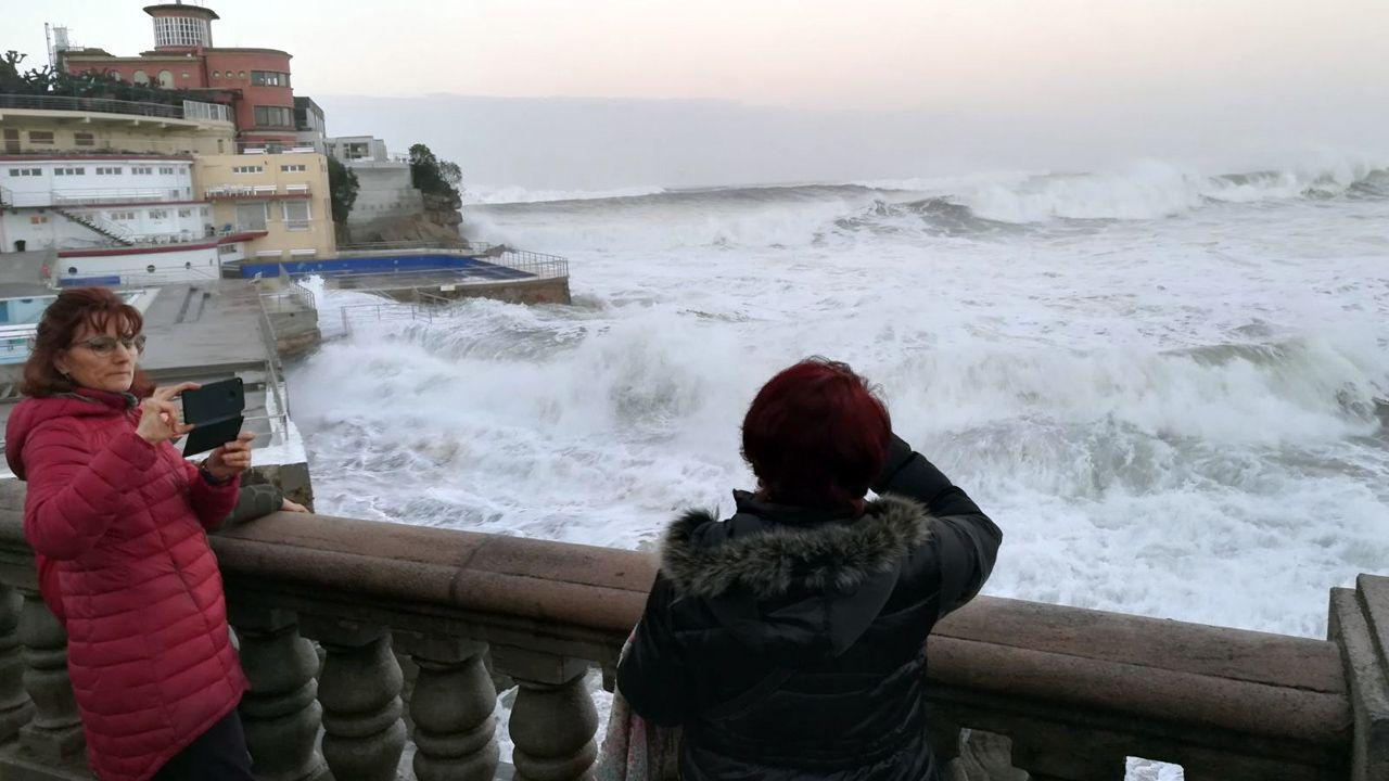 Gijoneses se asoman al Cantábrico, para ver los efectos del temporal Evi, y sacan fotografías junto al Club de Regatas.Gijoneses se asoman al Cantábrico, para ver los efectos del temporal Evi, y sacan fotografías junto al Club de Regatas