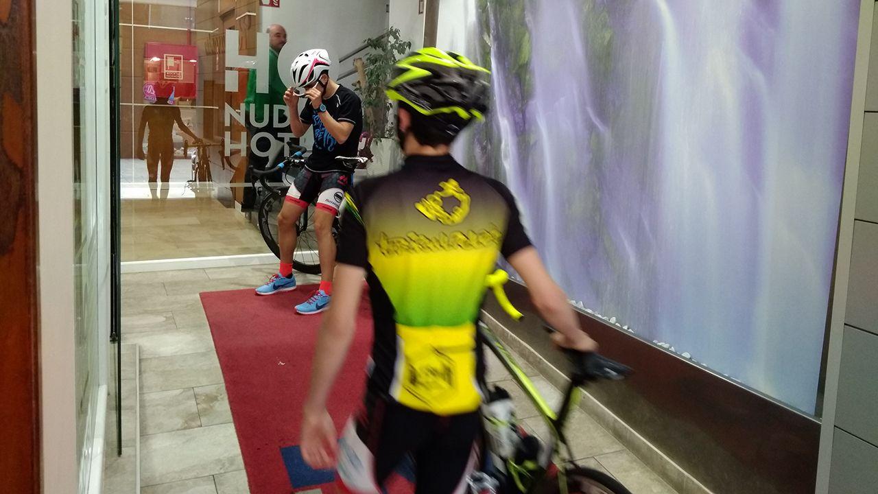 Dos duatletas entrando en un hotel del centro de Avilés tras un entrenamiento