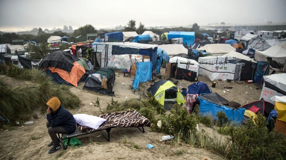 .Un inmigrante fala polo móbil durante a evacuación do campamento coñecido como a Xungla de Calais