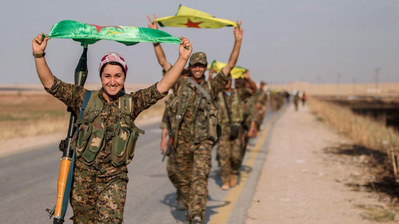 Combatientes  kurdos victoriosos ondean sus banderas amarillas en Tel Abyad, en la provincia de Raqqa (Siria) después de tomar el control de la zona. En primer término, una mujer soldado sonriente y portando un misil