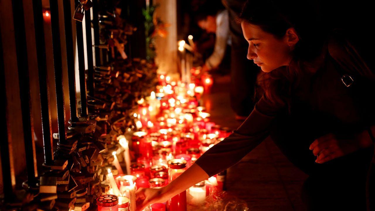 .Una mujer coloca una vela en el monumento Love durante una vigilia silenciosa a la luz de las velas para protestar contra el asesinato de la periodista