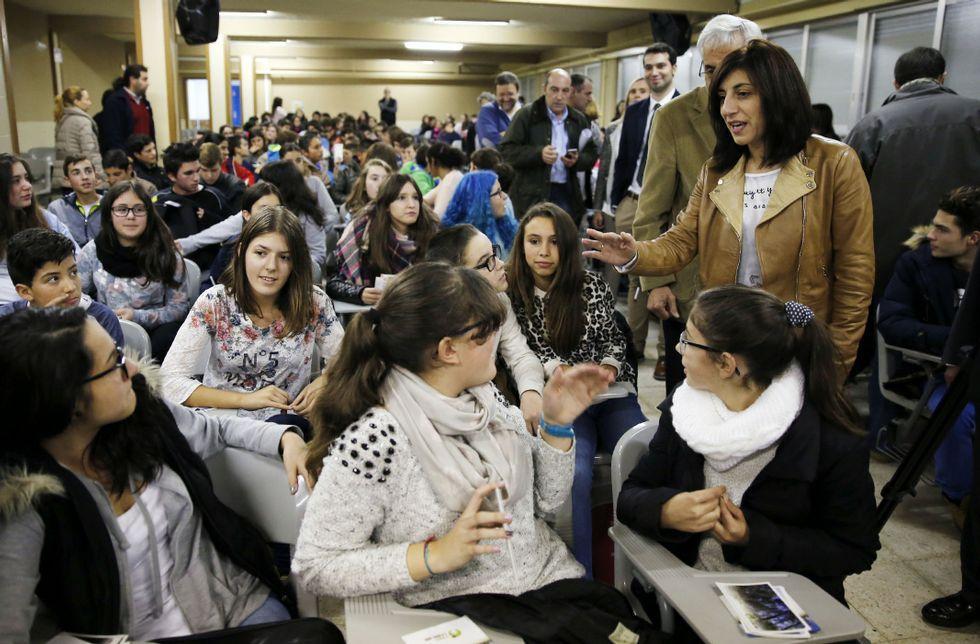 .La conselleira, de pie, saludando a los estudiantes a su entrada al salón de actos del instituto.
