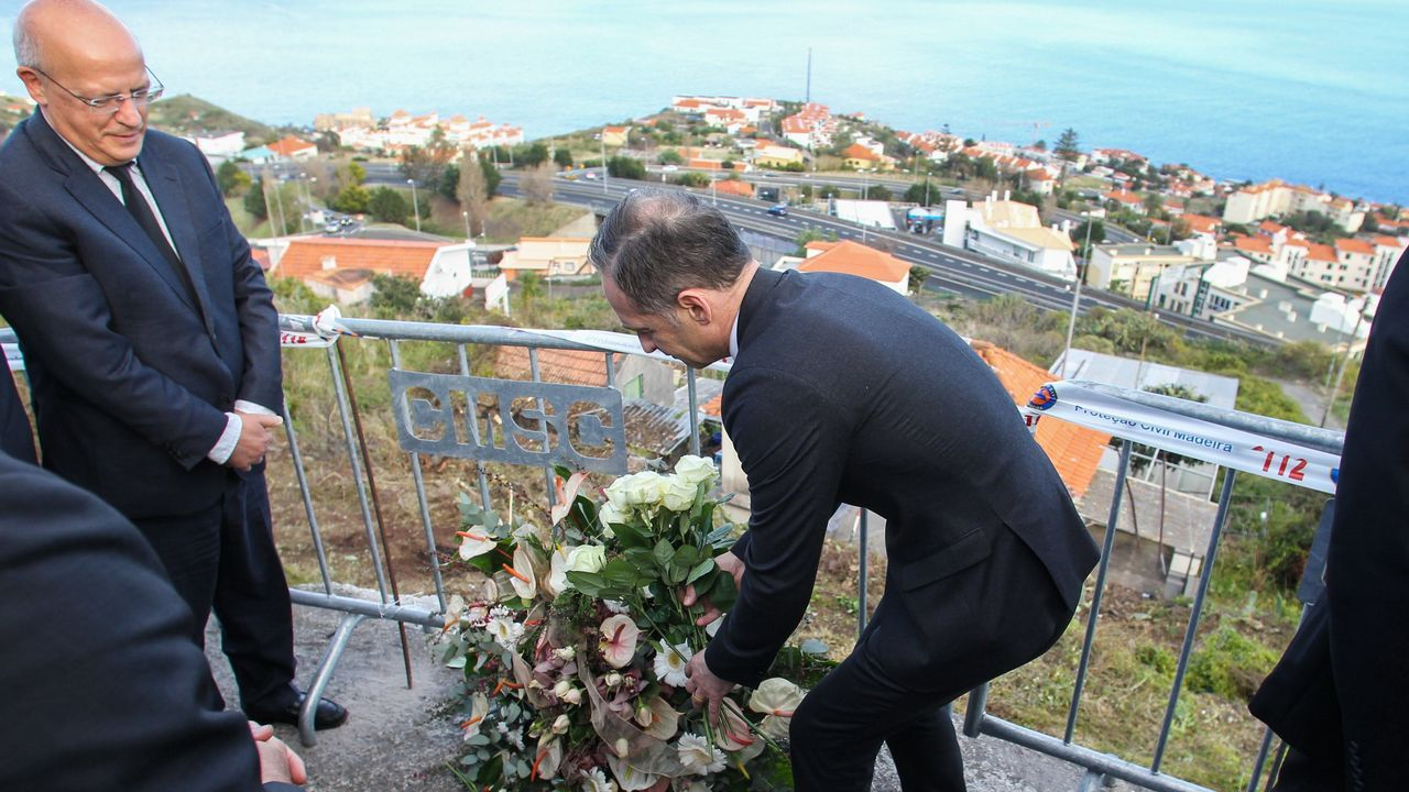 El ministro de Relaciones Exteriores de Alemania, Heiko Maas, deposita una corona de flores ante su homólogo portugués, Augusto Santos Silva,  durante una visita este jueves al lugar del accidente del autobús turístico, en Canico, Santa Cruz, Madeira (Portugal)