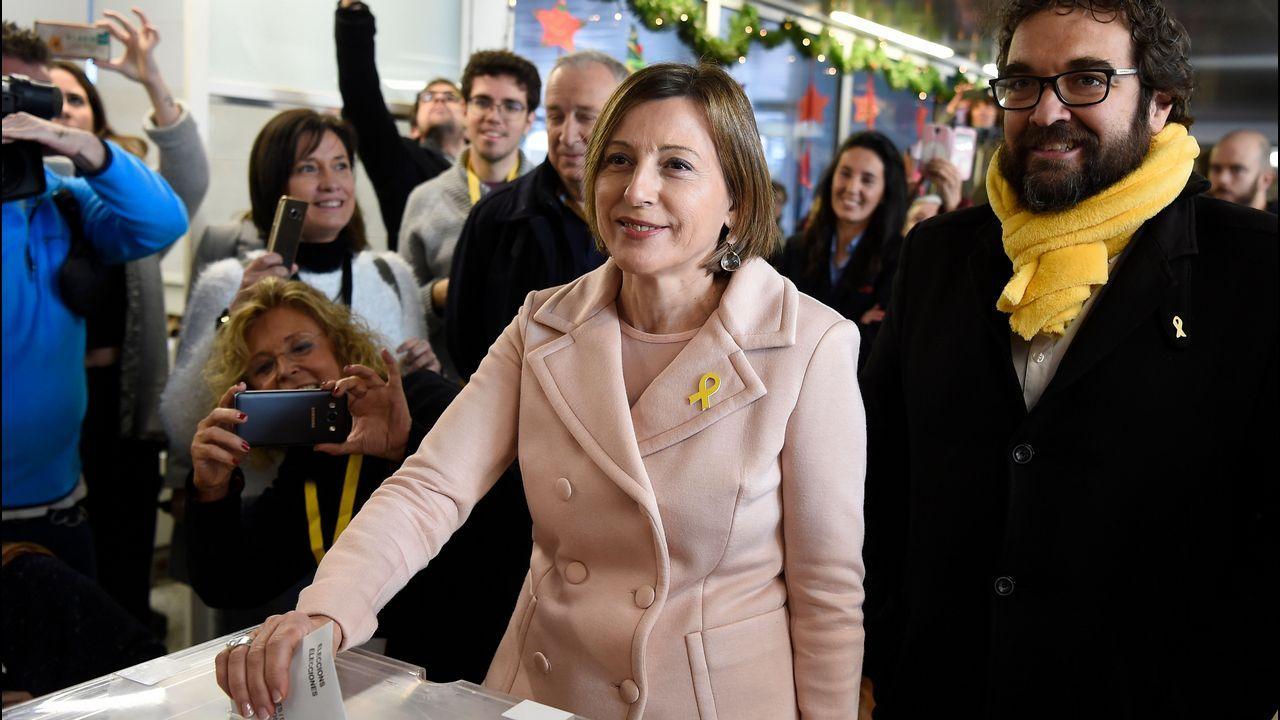 .Carme Forcadell votando con un lacito amarillo en la solapa de su abrigo.