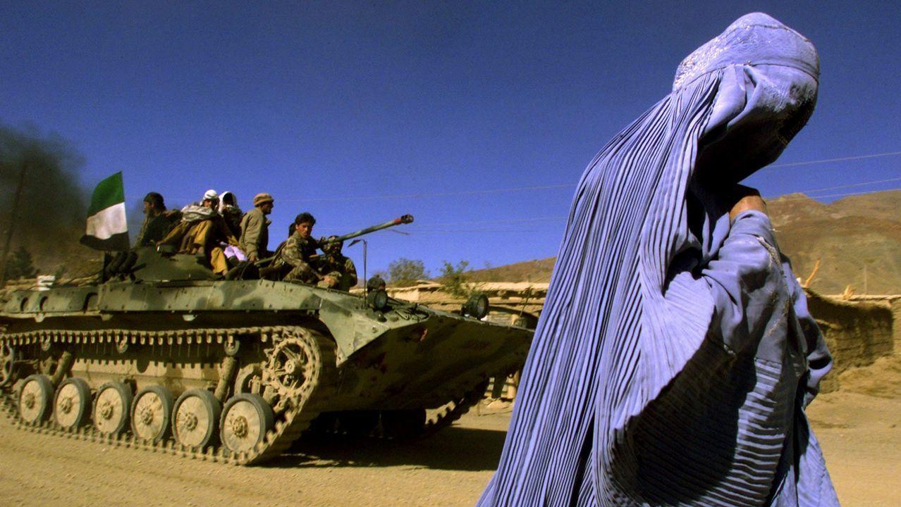 Una mujer vestida con burka camina junto a un tanque con una bandera afgana en Kabul