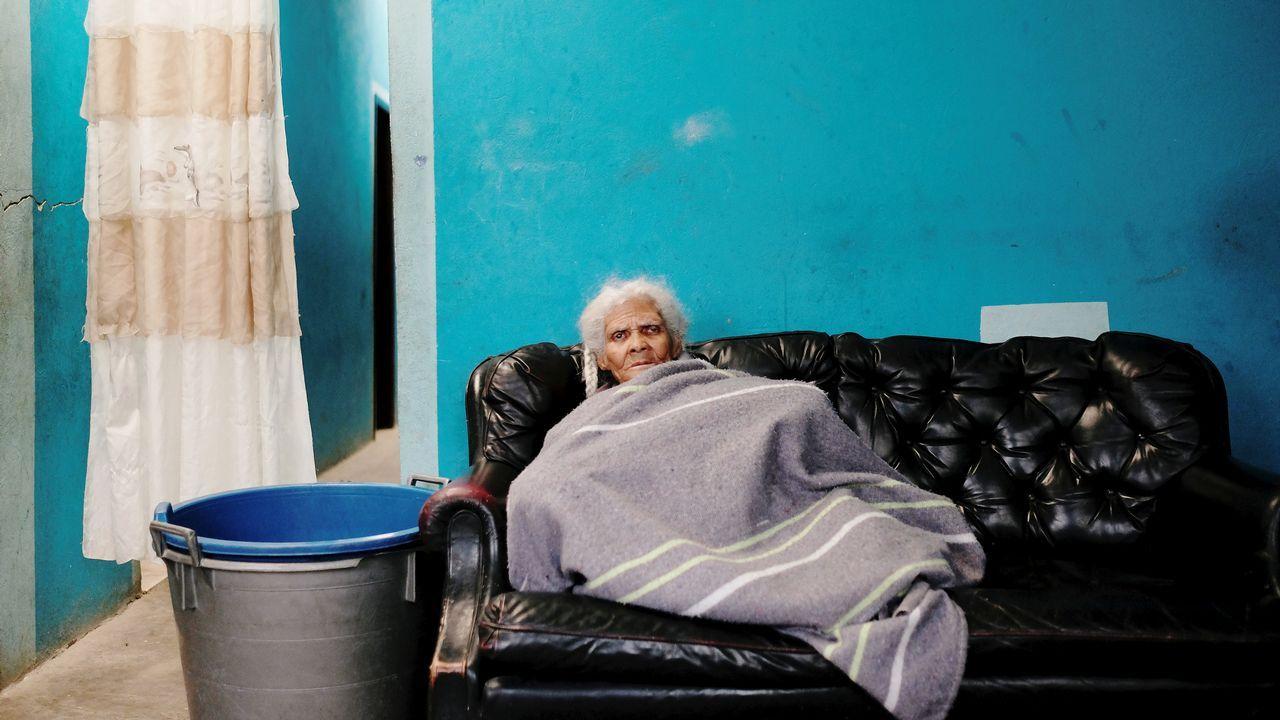 .Una anciana sentada en un sofá de su casa, en un suburbio de las afueras de Bogotá