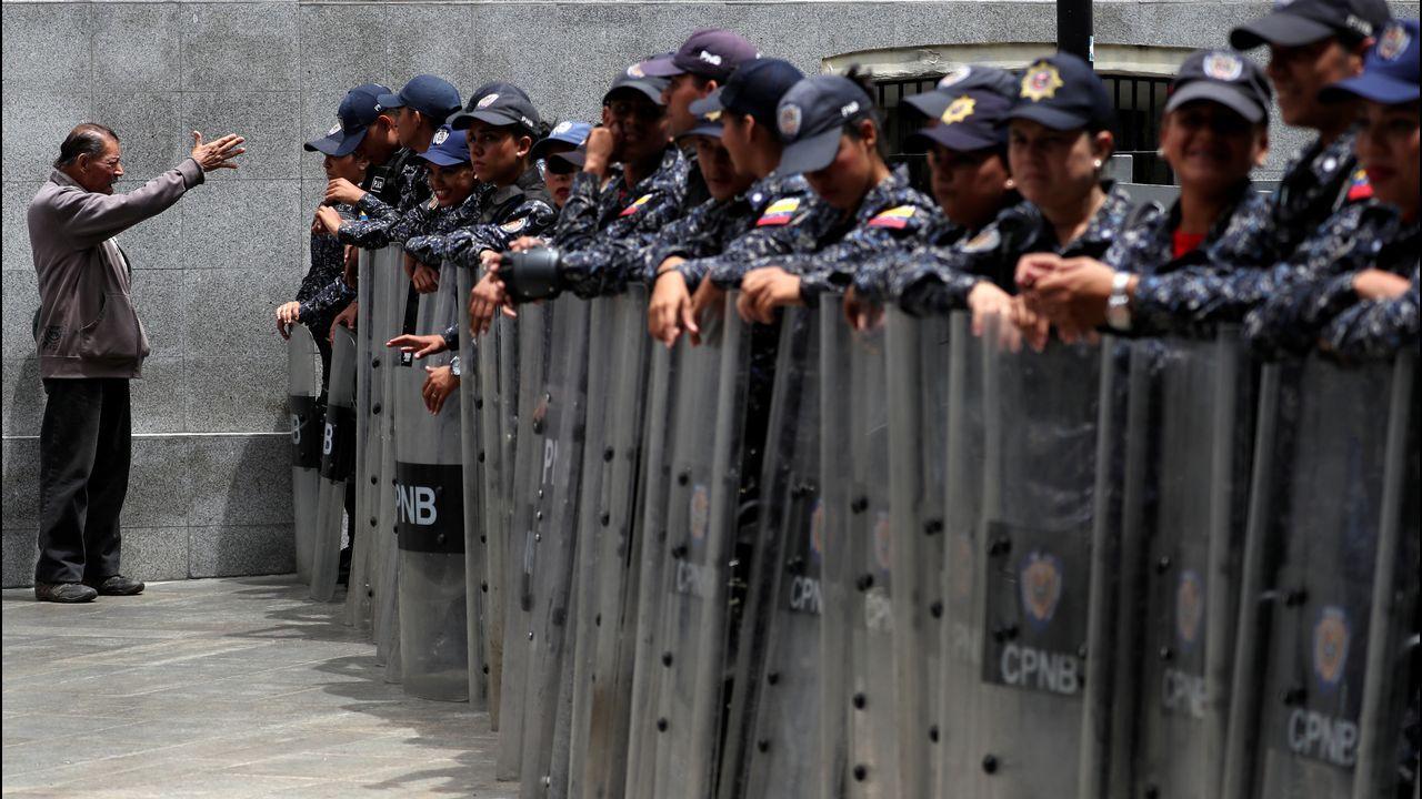Un hombre se dirige a los agentes del Sebin apostados en el exterior del Palacio Legislativo de Caracas
