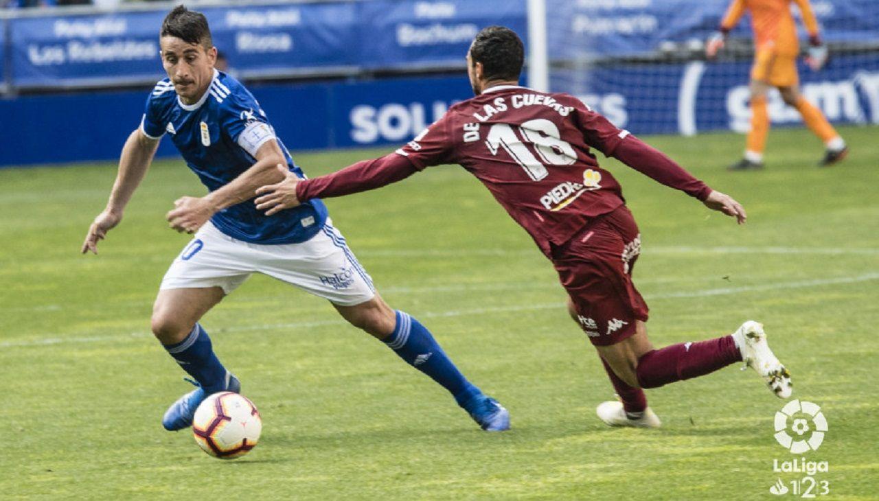 Saul Berjon De las Cuevas Real Oviedo Cordoba Carlos Tartiere.Saúl Berjón controla un balón ante la oposición de De las Cuevas